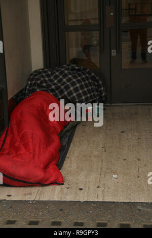 London, UK. 25th Dec, 2018: A homeless person sleeps by a doorway to a shop on Regents Street on Christmas day with no public transport running on 25th December 2018. Some parts of the city experienced dense fog which is expected to linger for the rest of the week. Credit: David Mbiyu/Alamy Live News - Stock Image