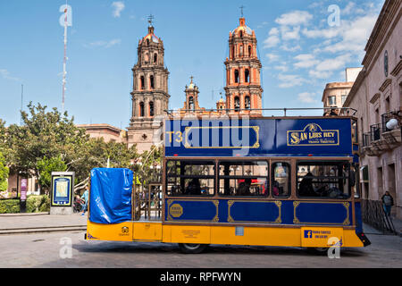 A quaint double decked tour bus passes the baroque facade of the Cathedral of San Luis Potosi in the historic center on the Plaza De Armas in the state capital of San Luis Potosi, Mexico. Also known as the San Luis Potosi Metropolitan Cathedral, it is consider the most important monument in the state and the first Baroque style building constructed in 1670 on the site of a parish church first built in 1593. - Stock Image