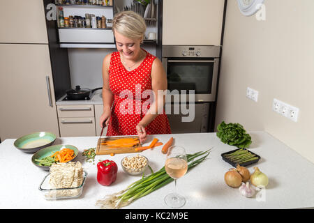Young girl chopping carrot on wooden cutting board - Stock Image