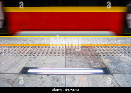 blurred red subway train, tactile paving also called detectable warning surfaces for visually impaired. yellow line, safety warning lamp - Stock Image