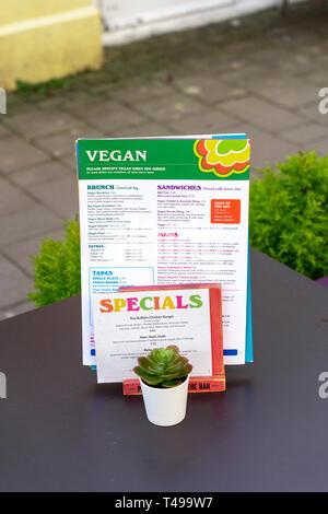 Vegan menu on restaurant table outside - Stock Image