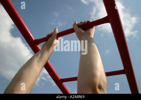 Holding onto monkey bars. - Stock Image