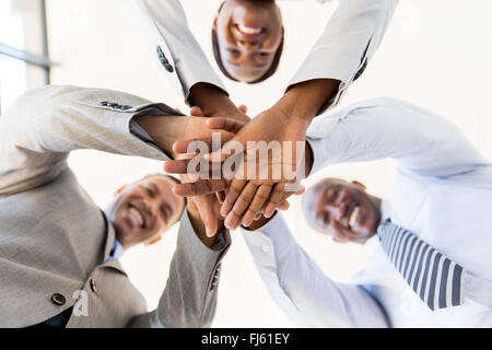 underneath view of business team hands together - Stock Image