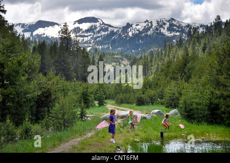 young girls butterfly butterflies mountain lake stream snow spring nets - Stock Image