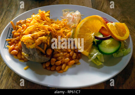 Cheap wholesome lunch jacket potato with cheese  baked beans coleslaw and salad - Stock Image