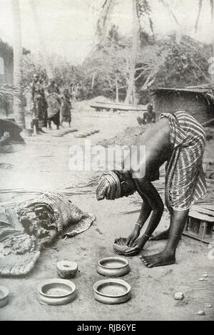 Woman of the Gold Coast (then part of the British Empire), West Africa, shaping clay around a stone mould to make pottery. - Stock Image
