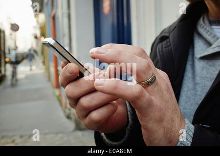 Mid adult man on sidewalk using touchscreen on smartphone - Stock Image