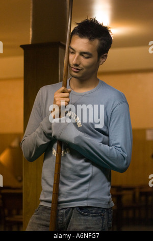 Bored young man leaning on a snooker cue with eyes closed in a Buenos Aires pool hall - Stock Image