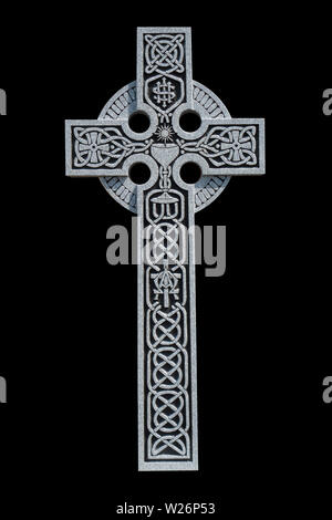 An ornate granite Celtic cross from the grave of a Roman Catholic priest, showing the Celtic knot pattern, a communion chalice, and the IHS symbol - Stock Image