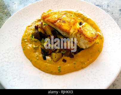 Halibut served with bacon mushrooms new potatoes and celeriac sauce seaside meal at the Seaview Café Saltburn North Yorkshire UK - Stock Image