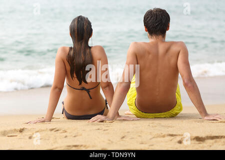 Back view portrait of a man and woman sitting on the sand watching sea on the beach watching ocean - Stock Image