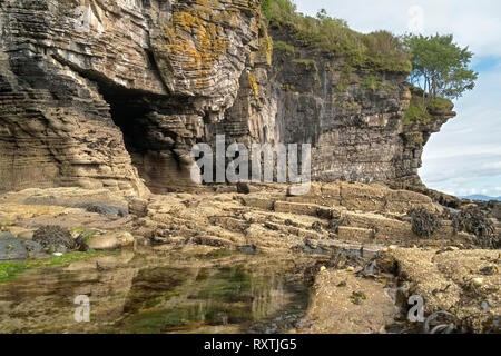 Eroded rocks sea cliffs and sea caves with rock pool on shoreline near Elgol on the Scottish Island of Skye, Scotland, UK - Stock Image