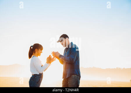 Father and daughter playing clapping hands game on the beach at sunset - Stock Image