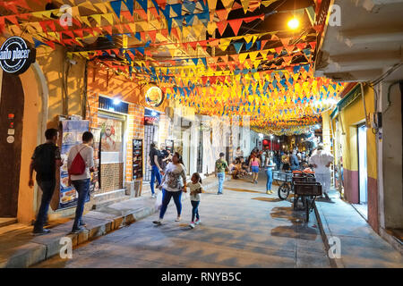 Cartagena Colombia Old Walled City Center centre Getsemani night nightlife Hispanic resident residents Calle San Andres colorful flags banners pedestr - Stock Image