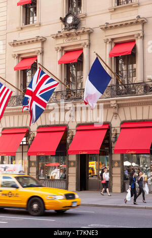 Taxi drives by Cartier Boutique on 5th Avenue in Manhattan, New York City, USA - Stock Image