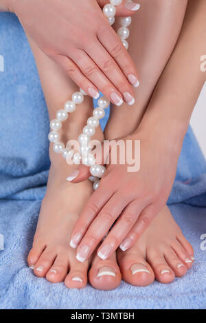 Manicure and pedicure woman legs with bare feet and hands holding pearls necklace on blue towel in healthy and spa salon. Girl with french nails - Stock Image