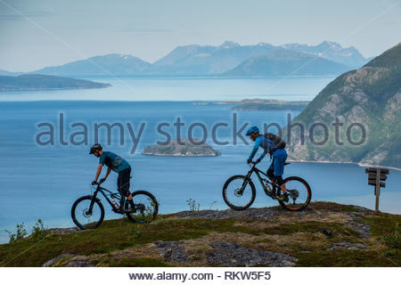 A man reads a book in the cabin of a catamaran as the sun sets behind a mountain bike on the deck on the Tromso Fjord during the summer months. - Stock Image