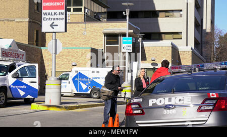 Toronto, Canada. 23rd Apr, 2018. CBC reporter tries to interview a police officer outside Ambulance Emergency entrance of Sunnybrook Hospital where 10 Alex Minassian van attack victims are receiving medical care in the afternoon of April 23, 2018. Credit: CharlineXia/Alamy Live News - Stock Image