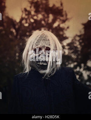 A white scary ghost zombie is outside at night with trees in the background for a decoration or halloween concept. - Stock Image