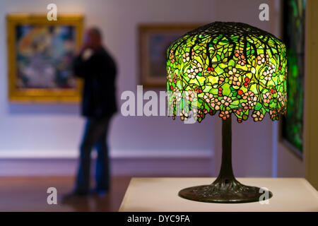 Roslyn, New York, U.S. - April 12, 2014 - Visitors view a Tiffany Studios stained glass table lamp, Chanson de printemps after Bouguereau, and other artwork in the Garden Party exhibit at the Nassau County Museum of Art on Long Island. Credit:  Ann E Parry/Alamy Live News - Stock Image