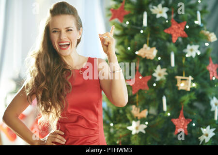 happy trendy woman in red dress near Christmas tree got idea - Stock Image