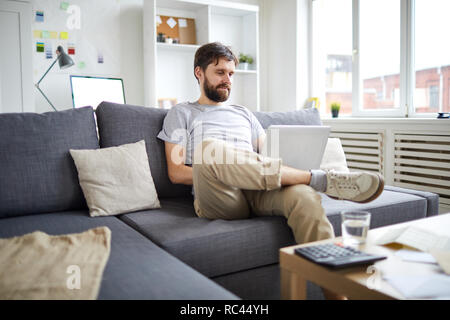 Young relaxed man sitting on sofa with laptop in front and watching webcast or scrolling in the net - Stock Image