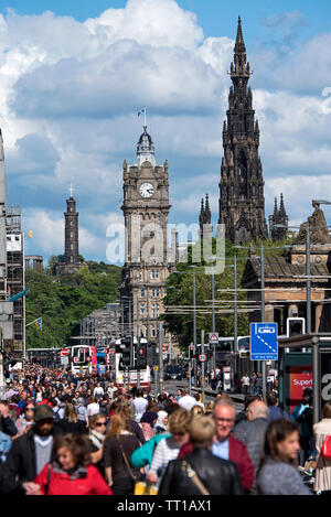 Looking along a busy Princes Street, Edinburgh, Scotland, UK. with the Scott Monument, Balmoral Hotel and Nelson's Monument in the background. - Stock Image