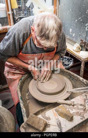 old man spinning potters wheel making clay plate,pilling,lancashire,england,uk - Stock Image