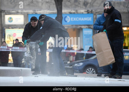 Prague, Czech Republic. 18th Sep, 2019. Investigators collect burnt clothes on the scene of the accident at upper part of Wenceslas Square in Prague, Czech Republic, where a man, born in 1964, poured combustible on him and set himself on fire on Friday, Jan. 18, 2019. The passers-by managed to put out the fire, his face and hands are burnt. Police inspect the incident. The paramedics told the media that the man suffered burns on 30 percent of his body. He was induced in artificial sleep and hospitalised. Credit: Ondrej Deml/CTK Photo/Alamy Live News - Stock Image