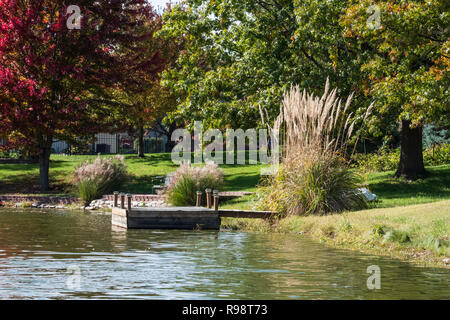A small private lake or pond with with pampas grass and boat or fishing dock in a neighborhood in Wichita, Kansas, USA. - Stock Image
