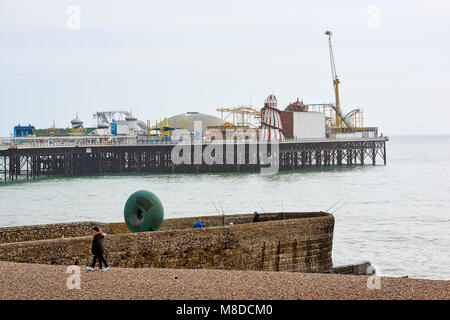 Side shot of Brighton pier, with people walking at the beach in the foreground. - Stock Image