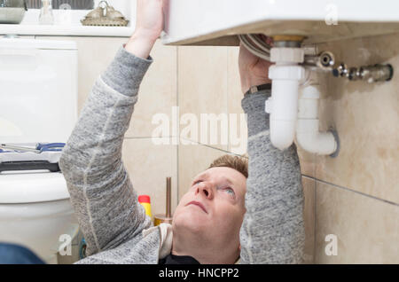 Young man attempting Do It Yourself (DIY) plumbing at home under a sink fitting a new tap. - Stock Image