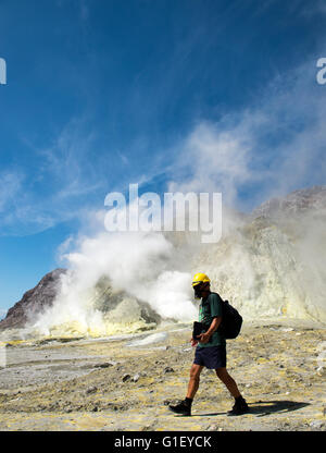 Tourist with gas mask and hard hat on land at active volcano Whakaari White Island New Zealand - Stock Image
