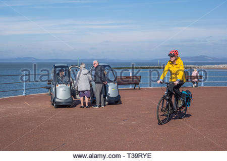 Cyclist, pedestrians and people in mobility scooters on Morecambe Promenade in the spring sunshine - Stock Image