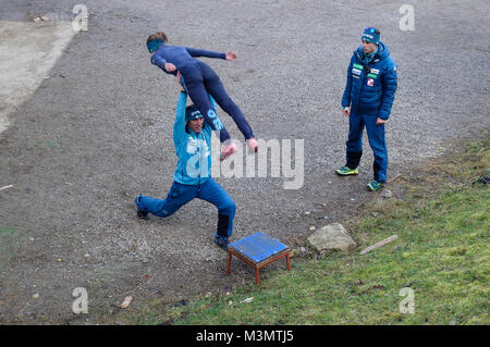 Ski jumping. A female competitor from Slovenian team checks the take off technique being helped by Primož Peterka - Stock Image