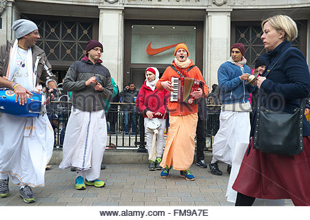 Members of Hare Krishna dance and sing as a passing pedestrian ignores them, on Oxford Street in central London, - Stock Image