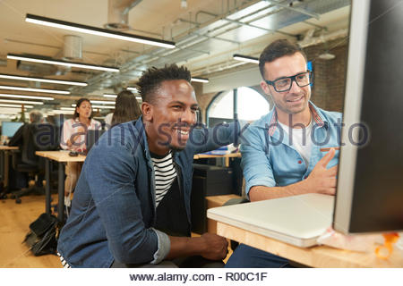 Smiling colleagues using computer - Stock Image