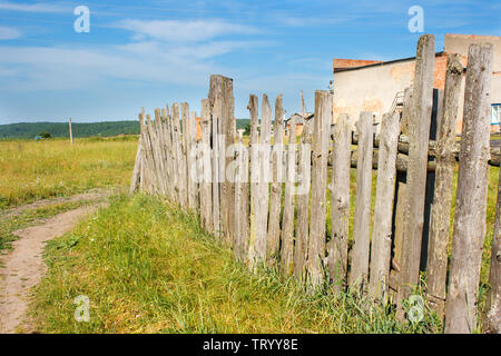 old wooden fence in the field in the village on sunny summer day - Stock Image