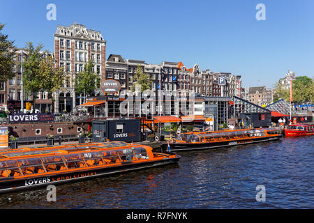 Tourist cruise boats at Open Havenfront canal in Amsterdam, Netherlands - Stock Image