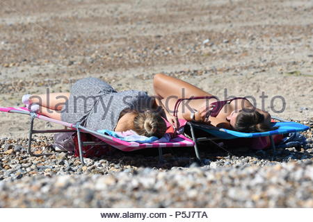 Littlehampton, UK. Wednesday 27th June 2018. Women laying in the beach in the sun using smartphones on another very warm and sunny morning in Littlehampton, on the South Coast. Credit: Geoff Smith / Alamy Live News. - Stock Image