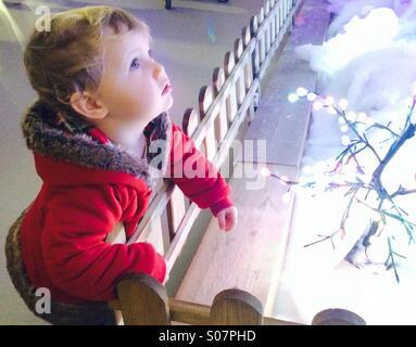 Little girl staring at Christmas lights in wonder - Stock Image