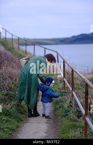 A mother and her son walking along a path by the sea in winter in Cornwall, UK - Stock Image