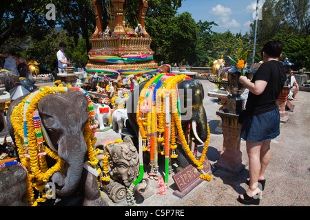 Thai Buddhists praying at open air Buddhist temple devoted to sacred elephants at Cape Promthep. - Stock Image