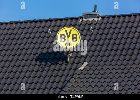 symbolic image, parabolic antenna in club colours and with club emblem of the German football club BVB 09 Borussia Dortmund on a house roof, television aerial, satellite TV, sports, football, Bundesliga, football mania, club loyalty, roofing tiles - Stock Image