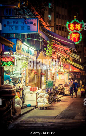 A laundry continues to work long after the market is closed for the night in Wan Chai, Hong Kong - Stock Image