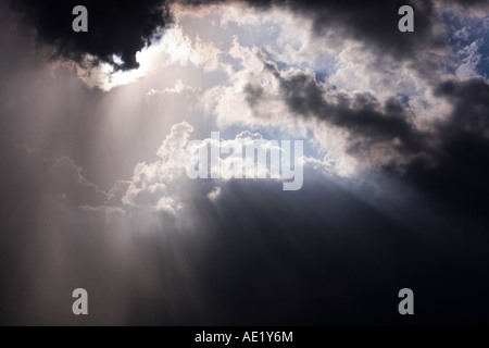 Rays of light breaking through dark clouds - Stock Image