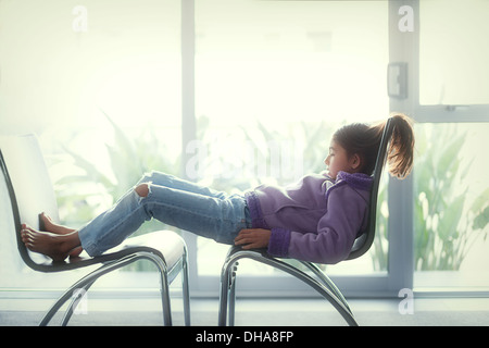 Girl lies back on two chairs - Stock Image