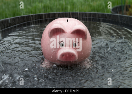 Pink Piggy bank getting wet in the rain - Stock Image