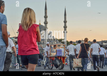 People walk on Galata Bridge. The minarets of the New Mosque (Yeni Camii) can be seen in the distance. - Stock Image