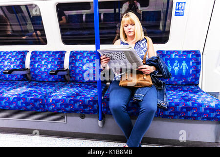 Woman reading paper on tube train, reading on London underground, reading newspaper, woman reading paper, traveling London underground, London UK - Stock Image